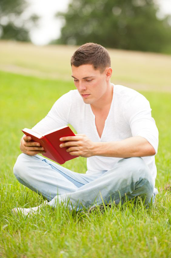 Young man sitting in the grass reading a book